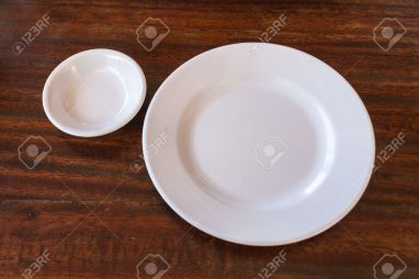Empty white plate and small chalice on wooden background